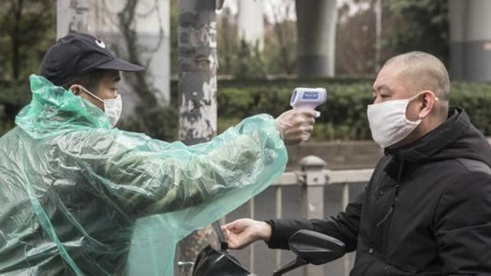 A security guard takes the temperature of a man wearing a protective mask at an entrance to a fresh produce market in Shanghai.