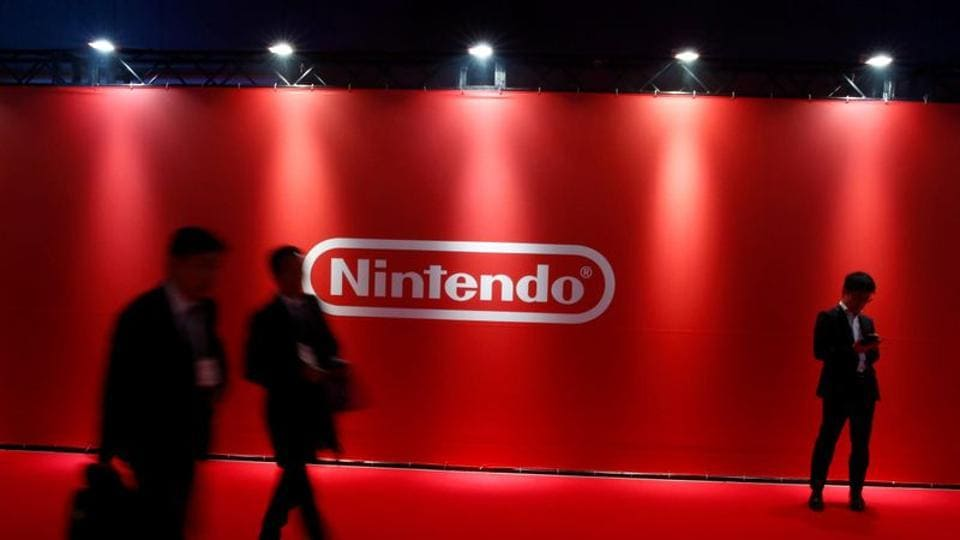 People stand in front of Nintendo's logo .