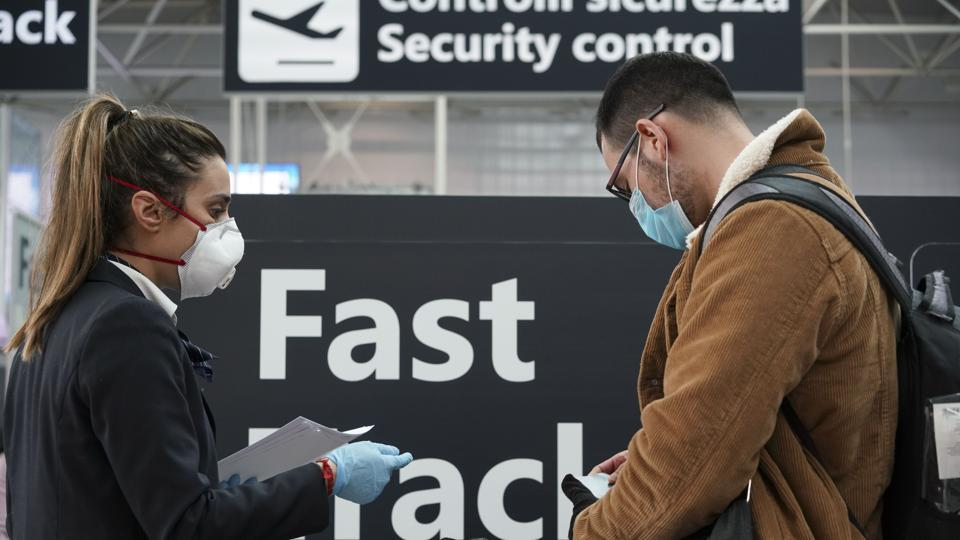 Ground staff gives information at the Rome Leonardo da Vinci international airport, Thursday, March 12, 2020. Italians woke up to yet further virus-containment restrictions after Premier Giuseppe Conte ordered restaurants, cafes and retail shops closed after imposing a nationwide lockdown on personal movement. For most people, the new coronavirus causes only mild or moderate symptoms, such as fever and cough. For some, especially older adults and people with existing health problems, it can cause more severe illness, including pneumonia. (AP Photo/Andrew Medichini)