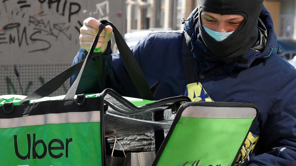 An Uber Eats food delivery courier closes a bag with an order during a lockdown, imposed to prevent the spread of coronavirus disease (COVID-19), in central Kiev, Ukraine April 2, 2020.